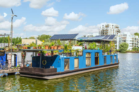 backwater: houseboat barge on a river with modern buildings in the background Stock Photo
