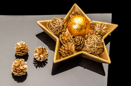 golden christmas decoration in a golden star-shaped bowl on a black acrylic  background