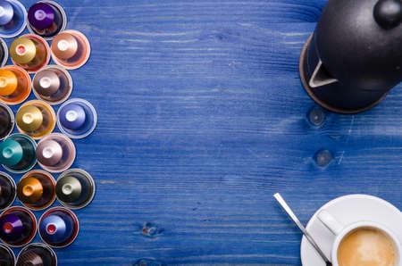 Espresso, cafetera espresso y cápsulas de café sobre un fondo de madera azul Foto de archivo