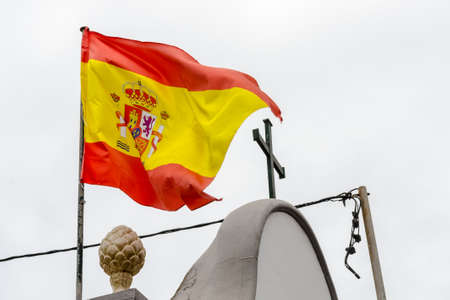 spanish flag and a christian cross on the top of a building Archivio Fotografico