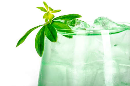 green woodruff drink with ice cubes on white background, isolated