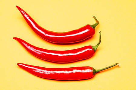 three red chilies on a yellow background 版權商用圖片