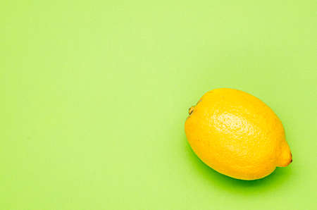 one yellow lemon on a green background 版權商用圖片