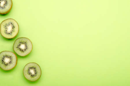 kiwis on a green pastel background, copy space