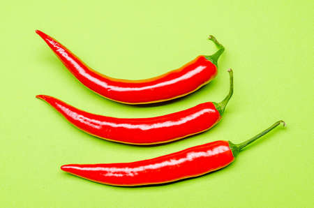 three red chilies on a green background