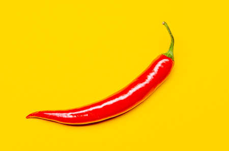 one red chili on a yellow background 版權商用圖片