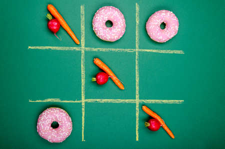 tic tac toe donuts vs. fruits on green background