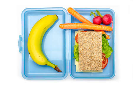 blue lunch box with bread, vegetables and banana on white background, isolated
