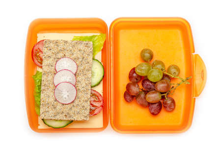orange lunch box with bread and vegetables on white background, isolated