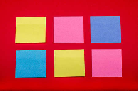 some coulored sticky notes on a red background Banco de Imagens