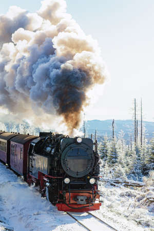 an old steam locomotive in snow-covered landscape
