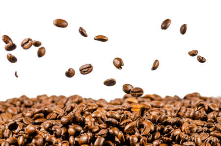 coffee beans fall on a heap of coffee beans, white background, isolated