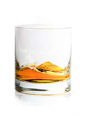 moved whiskey in a glass on white background