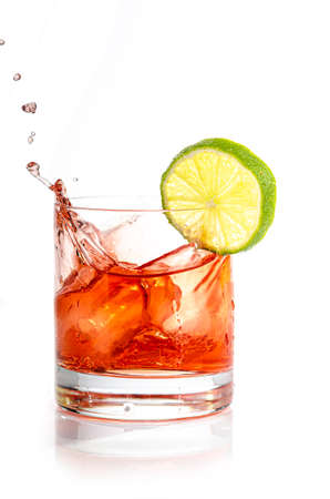 splashing red cocktail with ice cube and lemon slice Banco de Imagens