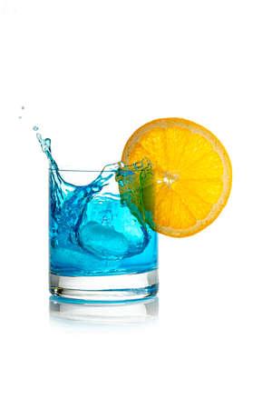 splashing blue cocktail with ice cube and lemon slice