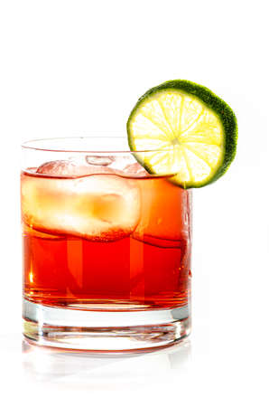 red drink with ice cubes and lemon on white background, isolated