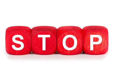 term STOP - built from red wooden cubes on white background, isolated