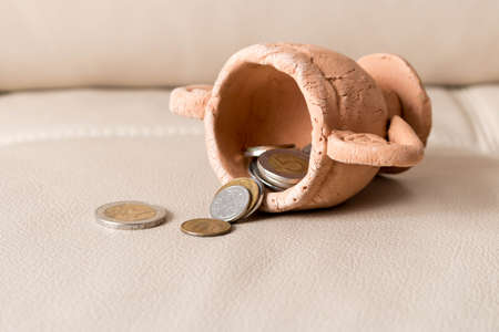 A lot of coins spill out of a clay Cup on a leather background.