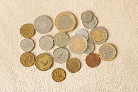 A lot of scattered coins on a leather background Stock Photo