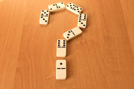Question mark of dominoes knuckles on wooden background.