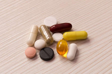 The pills are scattered on the table . On light background .