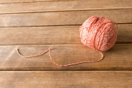 A ball of thread on the table . On the background of wooden table . Stock Photo
