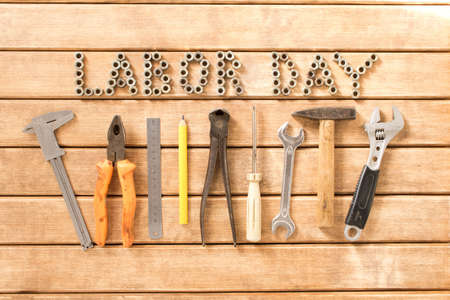 Labor day.  Different tools on a wooden table .