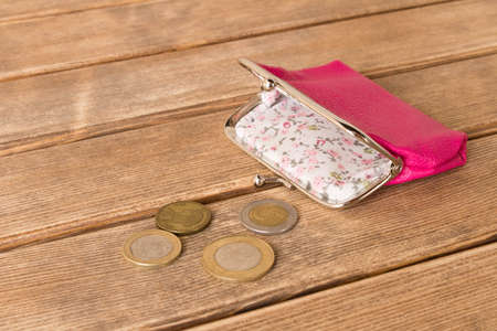 Wallet with coins on a wooden table . On wooden background .