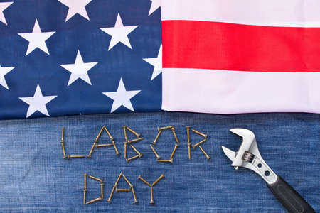 Labor day.   American flag.  Adjustable wrench.  On denim background . The concept of work .