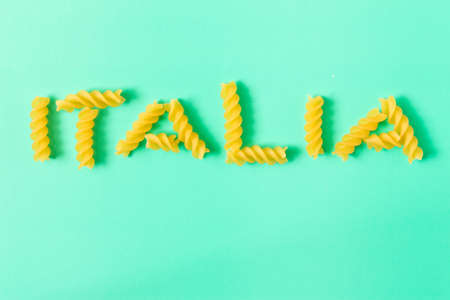 Uncooked fusilli pasta . The Inscription Italy . Isolated on turquoise background .