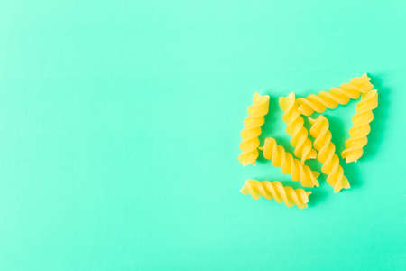 Uncooked fusilli pasta . Isolated on turquoise background . With empty space for text .