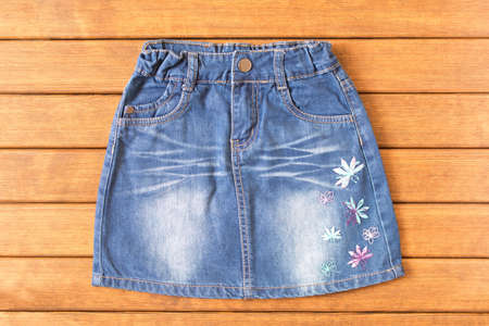 Children's denim skirt on wooden background . Children's clothes. Top view.