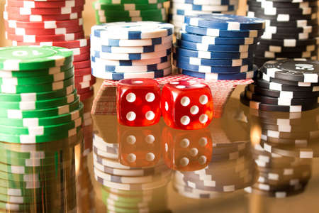 Dice and poker chips on the glass table. Casino concept. Stock Photo