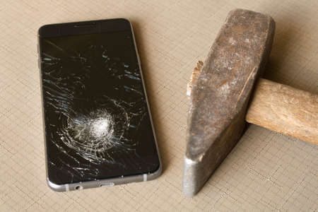 A broken cell phone and old hammer on grey background. Stock Photo