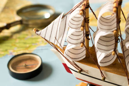 Model sailboat, compass and magnifying glass on map background. Travel concept.