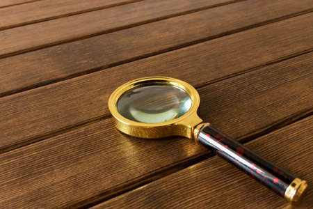 Magnifying glass on wooden table. Search concept. Stock Photo