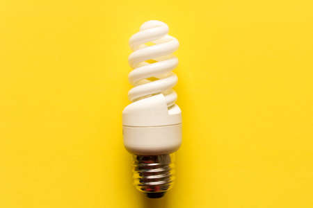 Energy saving lamp on yellow background. Close up. The concept of energy saving. Stock Photo