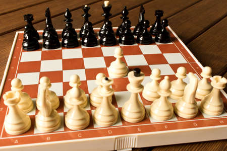 Black and white chess on a chessboard on a wooden table. Chess game concept. Stok Fotoğraf