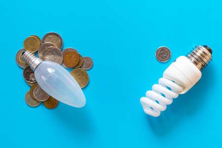 Energy-saving Lamp vs. incandescent lamp . Saving money. On a blue background . Stock Photo