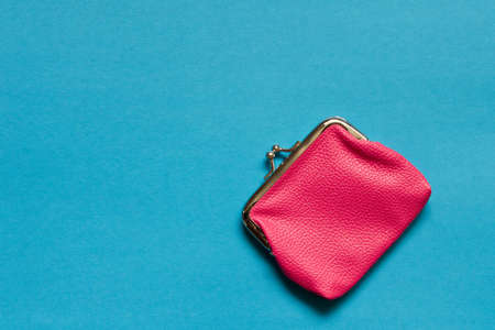 Pink wallet on blue background . Close up. Top view