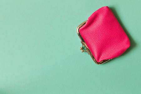 Pink wallet on turquoise background . Close up. Top view.