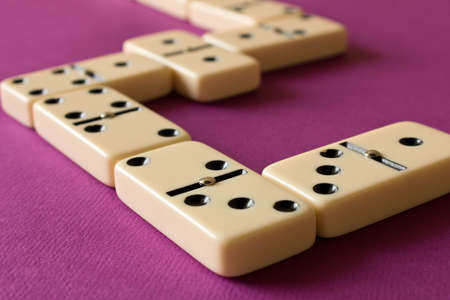 Playing dominoes on a purple background . The concept of the game of dominoes. Close up.