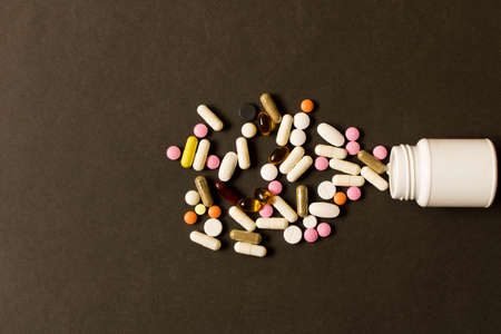 Open bottle with different pills on dark background. The view from the top.