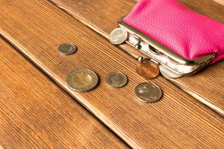 Wallet with coins on a wooden table . On wooden background.