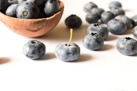 Fresh blueberries in a wooden spoon on a white background. Close up. The concept of natural food.