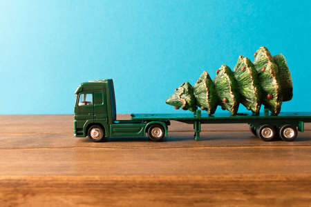 Miniature. Toy truck carries Christmas tree. The concept of Christmas. Empty space for text. Stock Photo
