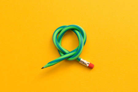 Flexible pencil . Isolated on yellow background. Imagens