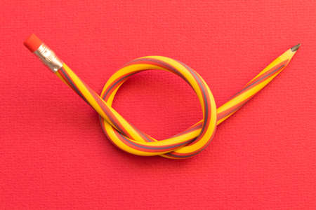 Flexible pencil . Isolated red background.