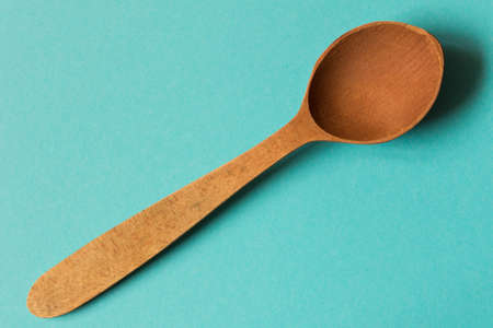 Old wooden spoon. Isolated on blue background .