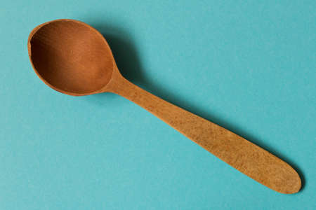 Old wooden spoon. Isolated on blue background.